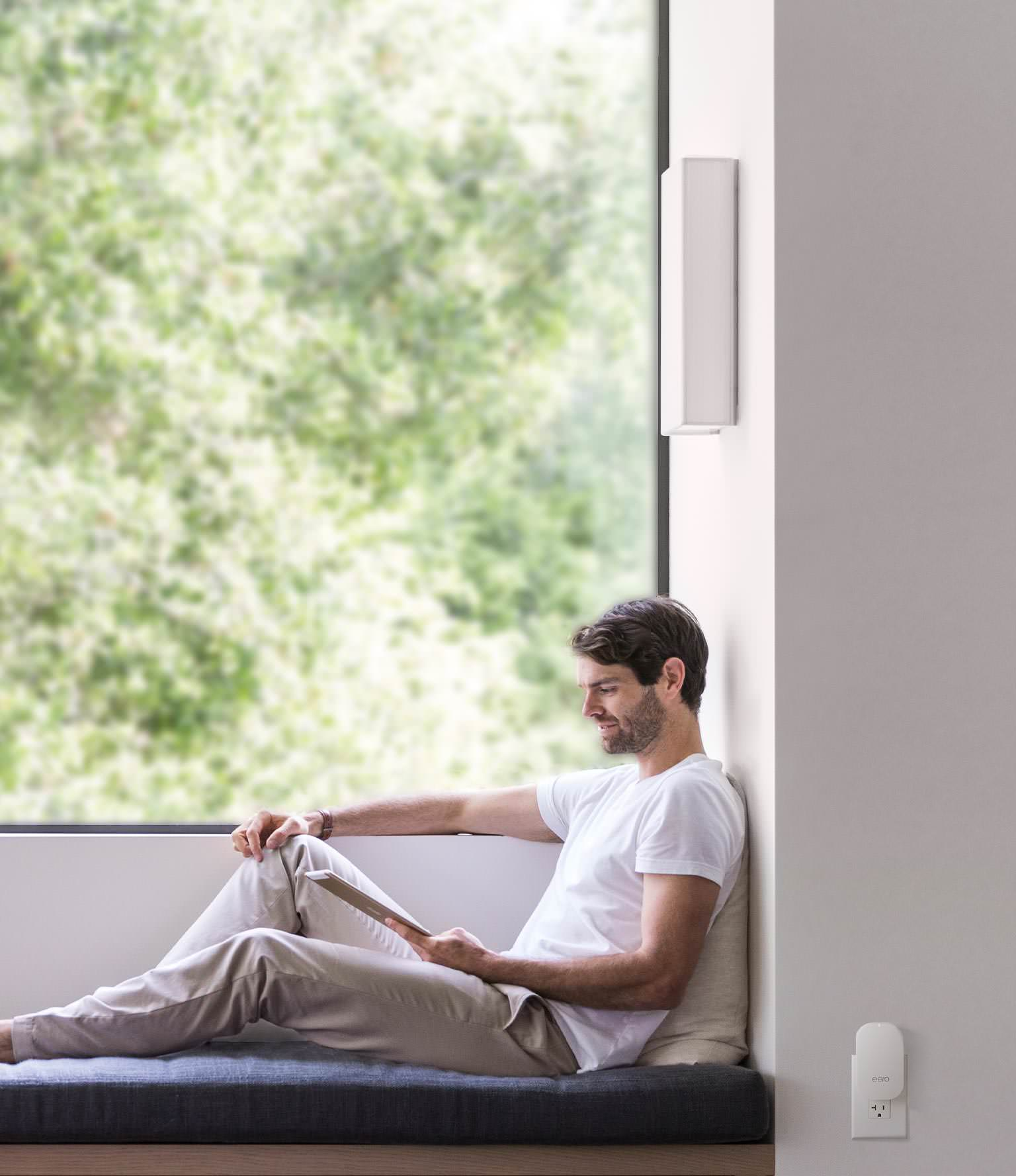 Man relaxing while using an iPad. An eero Beacon is nearby on the wall.